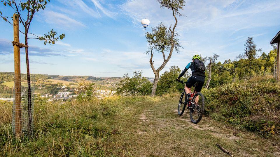 Mountainbiker, im Hintergrund ist ein Ort und am Himmel ein Heißluftballon zu erkennen